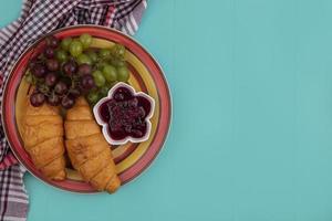 Croissants mit Trauben auf kariertem Stoff auf blauem Hintergrund foto