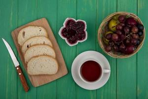 Tee mit Obst und Toast auf grünem Holzhintergrund