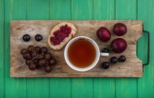 Tee mit Obst und Toast auf grünem Holzhintergrund foto