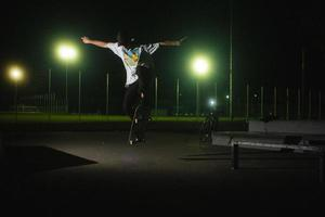 augsburg, deutschland, 2020 - junger mann skateboarding auf einem parkplatz bei nacht