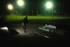 augsburg, deutschland, 2020 - junger mann macht nachts trickse auf einem skateboard