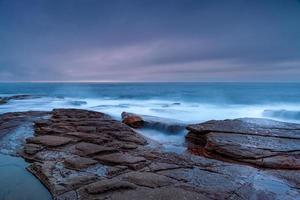 Langzeitbelichtung von Wellen bei Sonnenuntergang foto