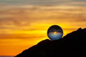 Glaskugel auf einem Felsen bei Sonnenuntergang
