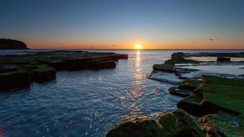 Moosfelsen nahe der Mündung des Ozeans während des Sonnenuntergangs