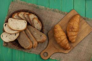 sortiertes Brot auf Sackleinen auf grünem Hintergrund