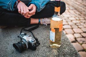 augsburg, deutschland, 2020 - person sitzt auf dem boden mit einer flasche wein und einer kamera