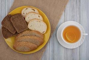 sortiertes Brot mit Tee auf hölzernem Hintergrund