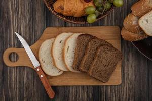 sortiertes geschnittenes Brot und Seiten auf hölzernem Hintergrund foto