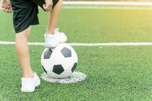 Füße eines Jungen, der weiße Turnschuhe trägt, die auf einen Fußball treten foto