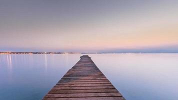 langer hölzerner Kai auf Garda See bei Sonnenuntergang foto