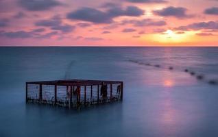 Seestück und leerer Käfig bei buntem Sonnenuntergang