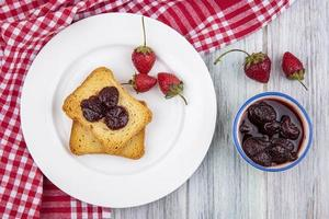 Toast und Frucht auf rotem Stoff auf grauem hölzernem Hintergrund