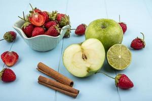 frisches Obst mit Zimtstangen auf blauem Grund foto