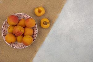 Aprikosen und Sackleinen auf neutralem Hintergrund mit Kopierraum