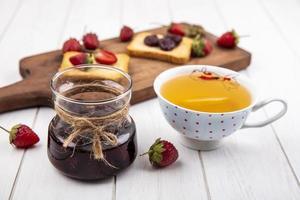 Tee mit Beerenmarmelade auf einem weißen hölzernen Hintergrund
