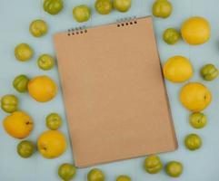 gelbe Pfirsiche, die einen Notizblock auf blauem Hintergrund umgeben foto
