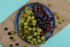 verschiedene Beeren auf Sackleinen auf blauem Hintergrund foto