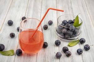 dunkle Beeren in einem Glas mit Blättern und rotem Saft
