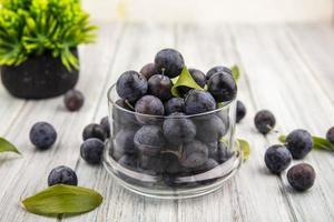 dunkle Beeren in einem Glas mit Blättern
