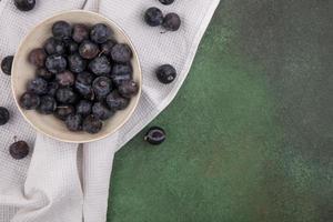 dunkle Beeren auf einem weißen Tischtuchhintergrund