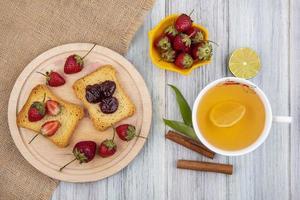Toast mit Obst und Tee auf einem grauen hölzernen Hintergrund