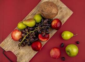 frisches Obst auf einem Holzbrett auf rotem Grund