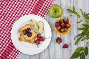 Toast mit Früchten auf rotem kariertem Stoff auf hölzernem Hintergrund
