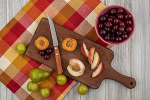 verschiedene Früchte auf kariertem Stoff auf hölzernem Hintergrund