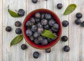dunkle Beeren in einer Schüssel auf hölzernem Hintergrund