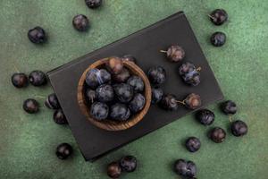 dunkle Beeren in einer Holzschale auf grünem Hintergrund foto