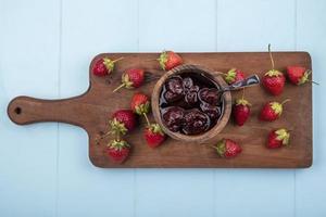 Erdbeeren und Marmelade auf hölzernem blauem Hintergrund