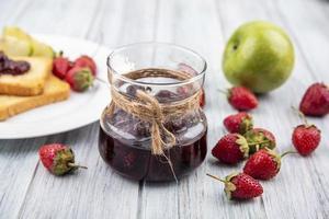 frisches Obst und Marmelade auf grauem hölzernem Hintergrund