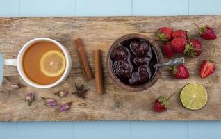Tee mit Beeren und Marmelade auf einem hölzernen blauen Hintergrund