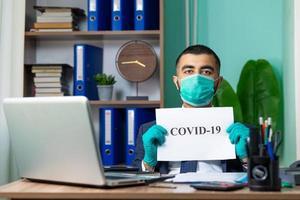 Mann an einem Schreibtisch mit Covid-19-Schild