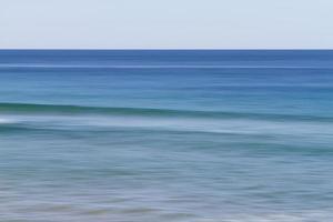 Langzeitbelichtung von Meereswellen während des Tages foto