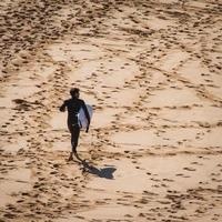 Sydney, Australien, 2020 - Mann, der mit einem Surfbrett auf einem Strand geht