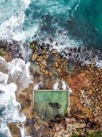 Luftaufnahme von Wellen, die auf Felsen krachen foto