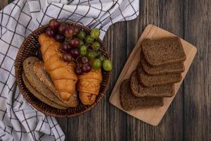 Obst und Brot auf kariertem Stoff auf hölzernem Hintergrund