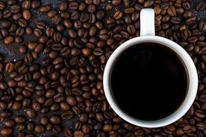 Draufsicht einer Tasse Kaffee auf braun gerösteten Kaffeebohnenhintergrund