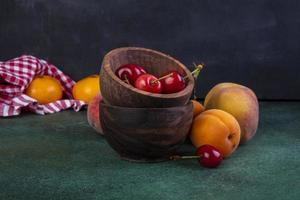 Vorderansicht von Pfirsichen mit Aprikosen und Kirschen in Schalen foto