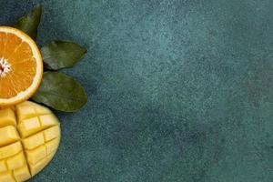 Draufsicht der geschnittenen Mango mit einer halben Orange auf einem grünen Hintergrund