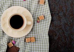 Draufsicht auf eine Tasse Kaffee und braune Zuckerwürfel