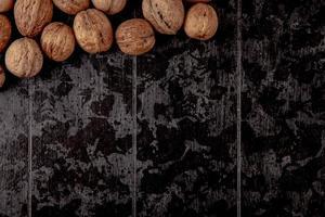 Draufsicht der ganzen Walnüsse verstreut auf schwarzem Hintergrund foto