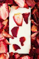 Draufsicht der weißen Schokoladentafel auf getrocknetem Erdbeerscheibenhintergrund