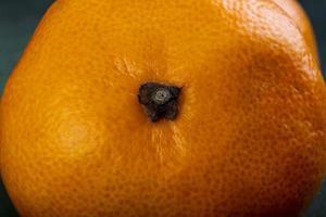 Nahaufnahme Vorderansicht der Mandarine auf einem grünen Hintergrund