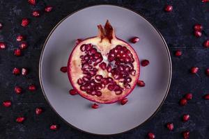 Draufsicht des geschnittenen Granatapfels auf einer weißen Platte auf einem schwarzen Hintergrund foto