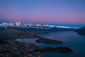 Sonnenuntergang über Fluss und schneebedeckten Bergen