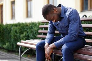 müder Mann sitzt draußen auf der Bank