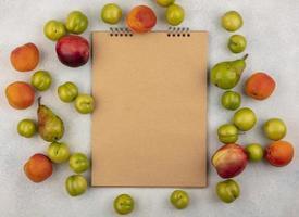 Draufsicht der Frucht um Notizblock auf weißem Hintergrund mit Kopienraum foto