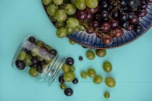Draufsicht auf Traubenbeeren, die aus Glas heraus verschütten
